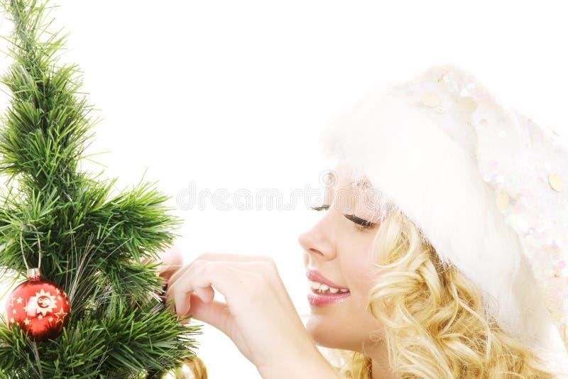 jul som dekorerar den flickahjälpredasanta treen arkivbild