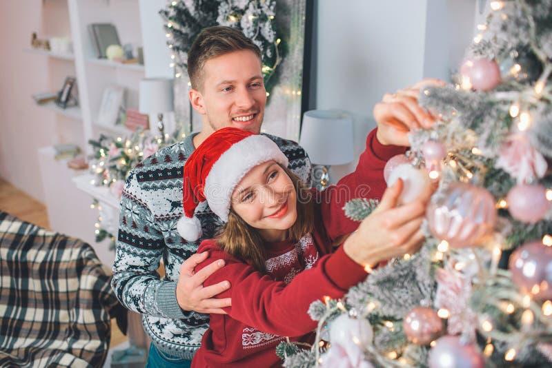 jul som dekorerar treekvinnabarn Hon trycker på leksaken på den Ställningar för ung man bakom och att omfamna henne De ler arkivbild