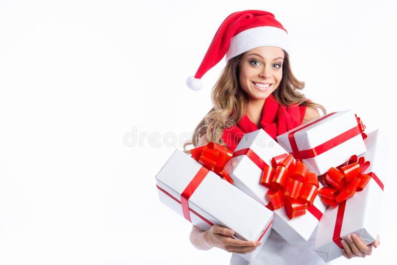 Jul som shoppar kvinnan som rymmer många julgåvor i hennes armar som bär den santa hatten royaltyfria bilder