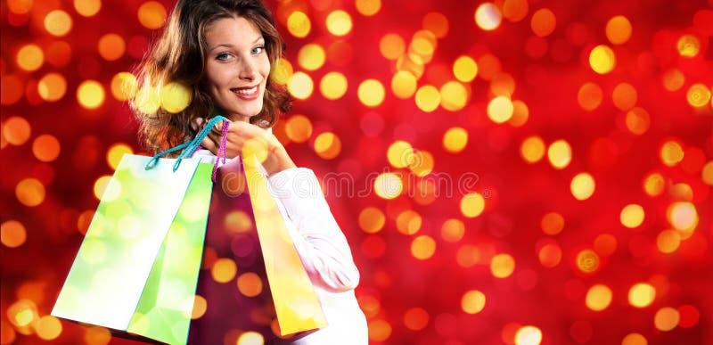 Jul som shoppar och att le kvinnan med påsar på suddig ljus li fotografering för bildbyråer