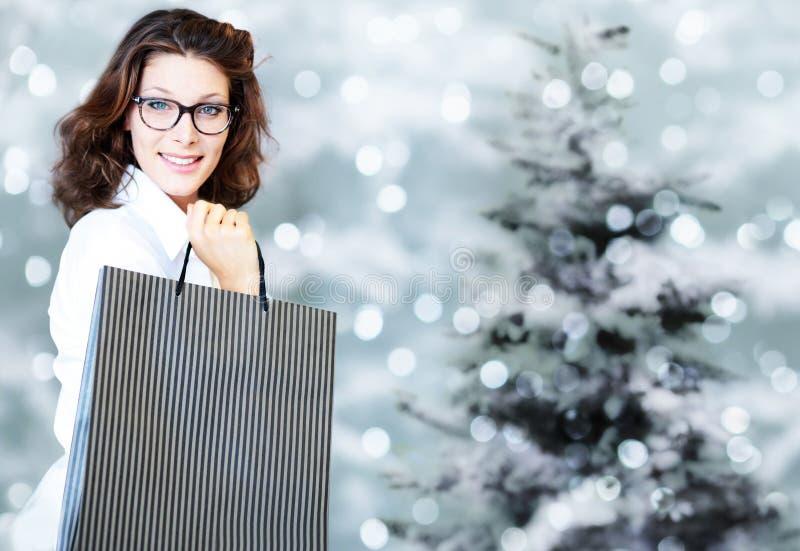 Jul som shoppar och att le kvinnan med påsar på suddig ljus li royaltyfri fotografi