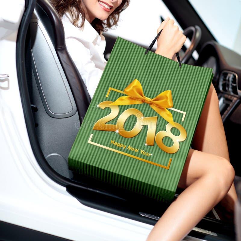 Jul som shoppar och att le kvinnan med påsen, får i bilen och mumlen fotografering för bildbyråer