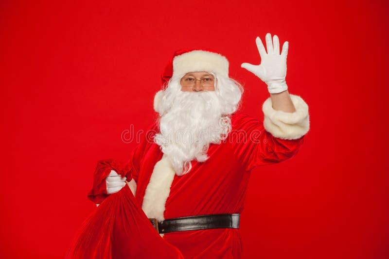 Jul Stående av Santa Claus med den enorma röda säckhanden upp att se ca arkivfoto