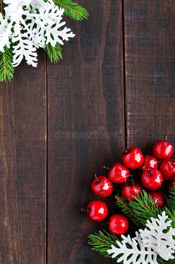 Jul tema för nytt år Gröna prydliga filialer, dekorativa bär, snöflingor på en mörk träbakgrund arkivfoton