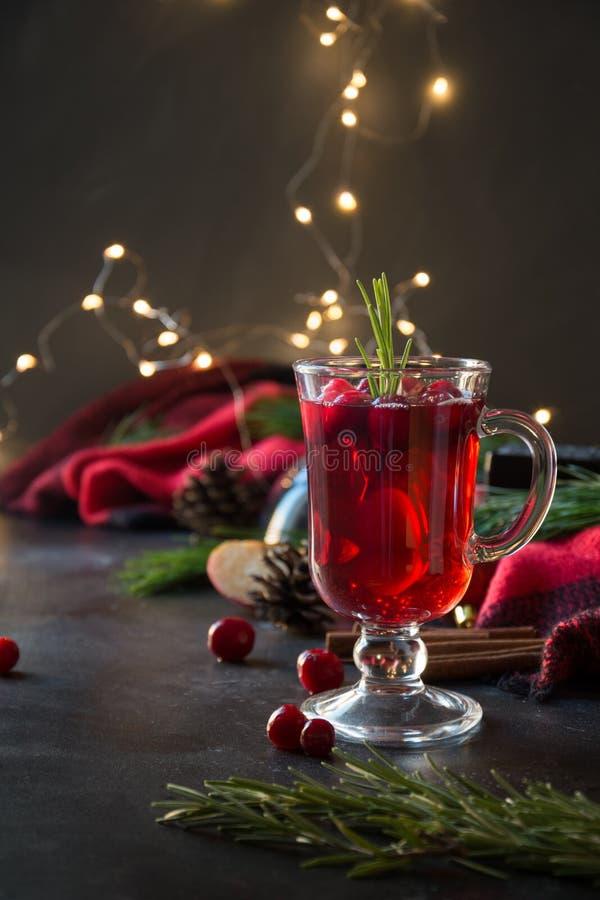 Jul tranbär och äpple funderade vingarneringrosmarin och granfilialer på svart Xmas-drink arkivbild