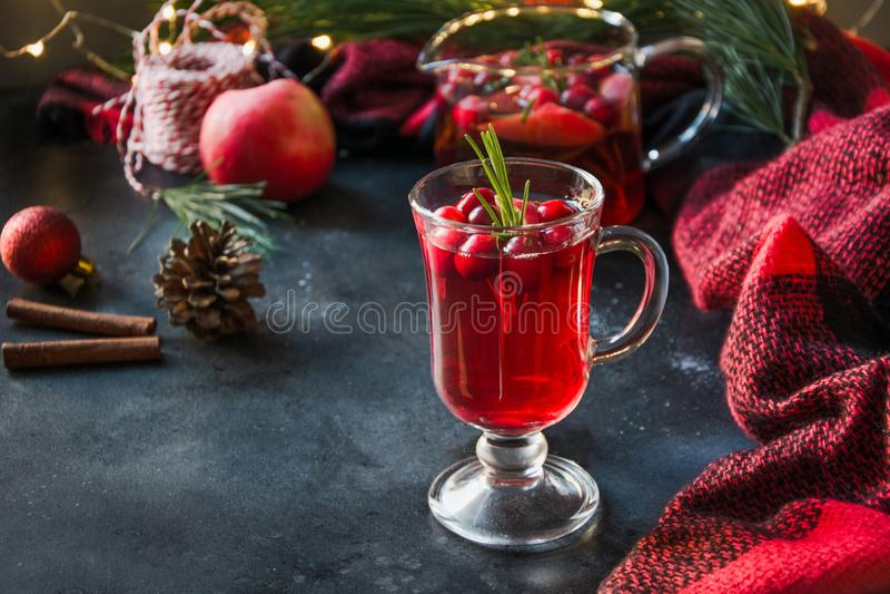 Jul tranbär och äppledrinken garnerar rosmarin, och gran förgrena sig på svart close upp Xmas-drink royaltyfria bilder