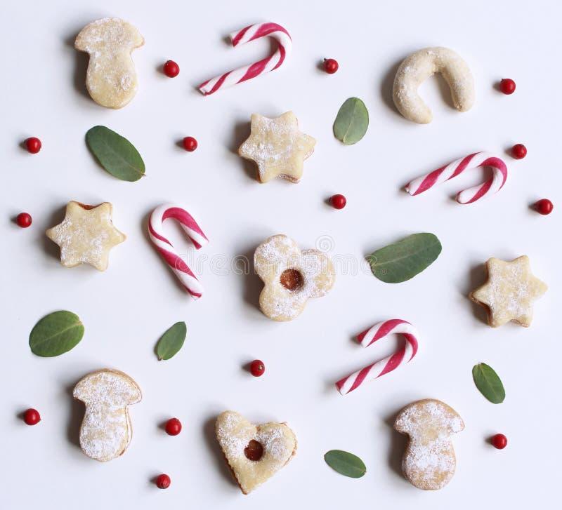 Jul utformad materielsammansättning Godisrotting, hemlagade festliga sötsaker och eukalyptussidor på vit bakgrund plant arkivbilder