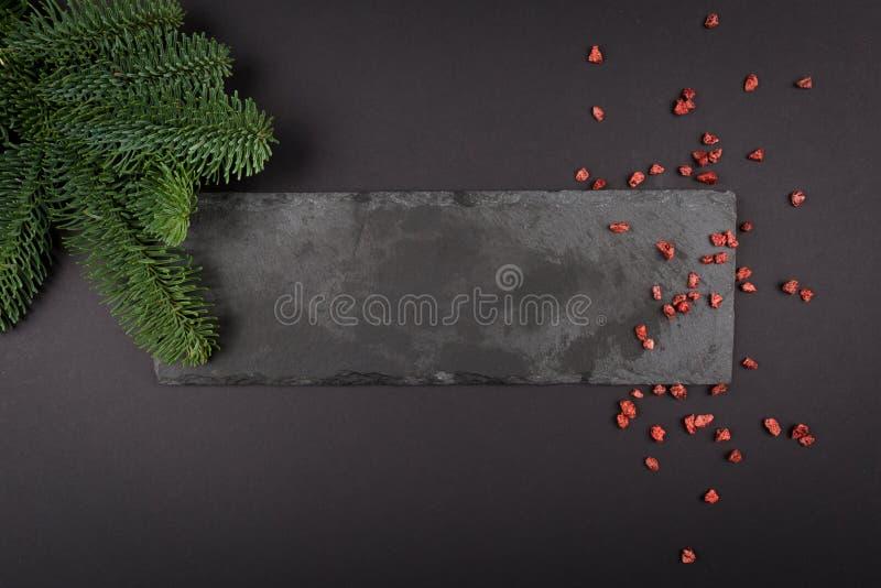 Jul utformade sammansättning, dekorativt kopieringsutrymme Mörkt juljärnekträd - gräsplan och rött blänker på svart tabellbakgrun arkivbilder