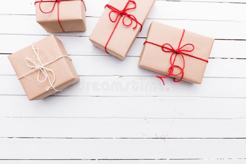 Jul utformar den lantliga packen för brunt papper som binds upp med rader Vit Wood bakgrund royaltyfria foton