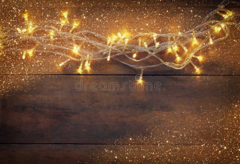 Jul värme guld- girlandljus på trälantlig bakgrund den filtrerade bilden med blänker samkopieringen arkivfoton