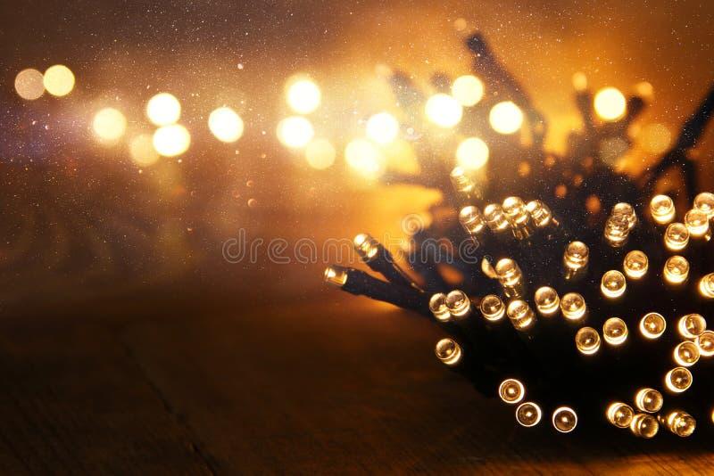 Jul värme guld- girlandljus på trälantlig bakgrund Filtrerad bild arkivfoto