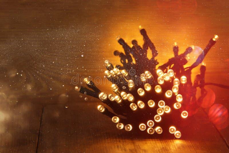 Jul värme guld- girlandljus på trälantlig bakgrund Filtrerad bild royaltyfri foto