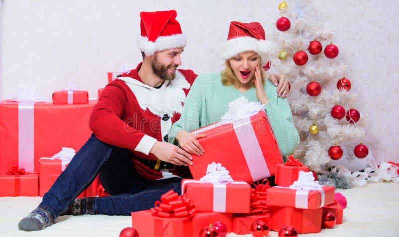 Julafton med älskling Kvinna och skägd man sitter nära julgranens trädbakgrund Kärlek är den bästa gåvan Familj royaltyfri bild