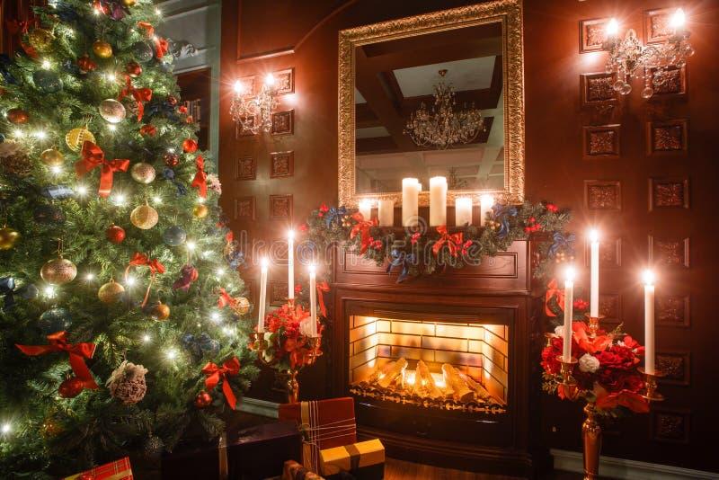 Julafton vid levande ljus klassiska lägenheter med en vit spis, ett dekorerat träd, soffa, stora fönster och royaltyfri fotografi