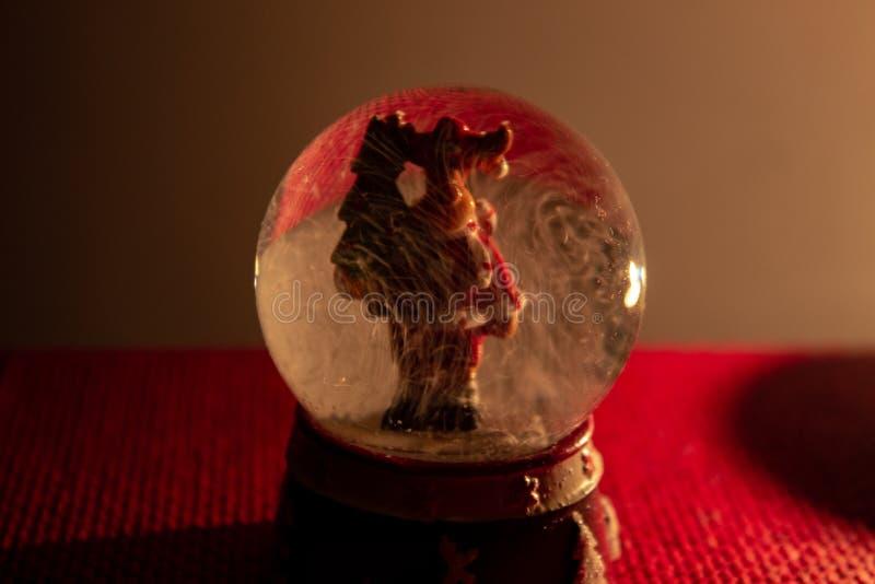 Julatmosfären av en exponeringsglasboll med en ren inom royaltyfria bilder