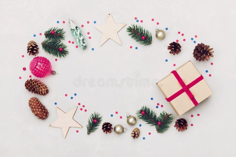 Julbakgrund av gåvaasken, granträdet, barrträdkotten och feriegarneringar på den vita bästa sikten för tabell Lekmanna- utforma f arkivbilder