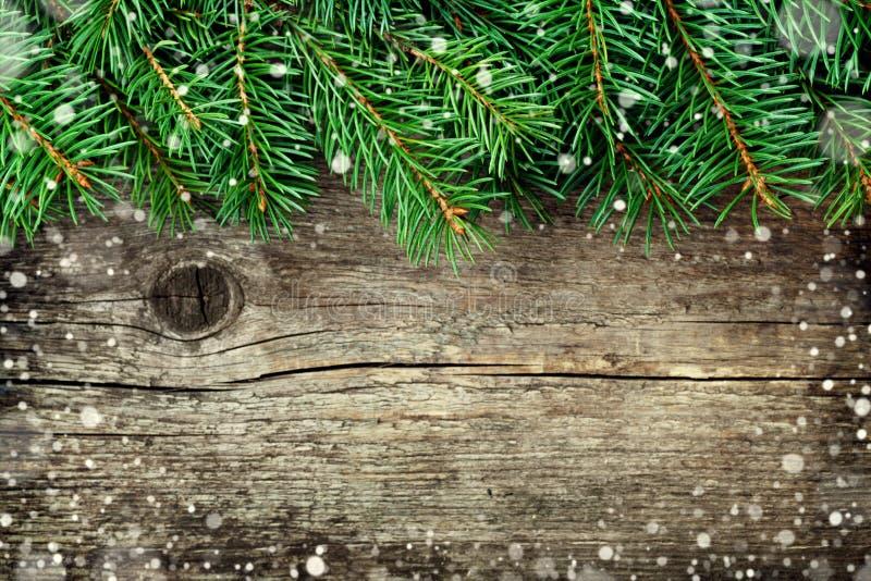 Julbakgrund av granträdet på träbrädet för gammal tappning, fantastisk snöeffekt, kopieringsutrymme för text royaltyfria foton