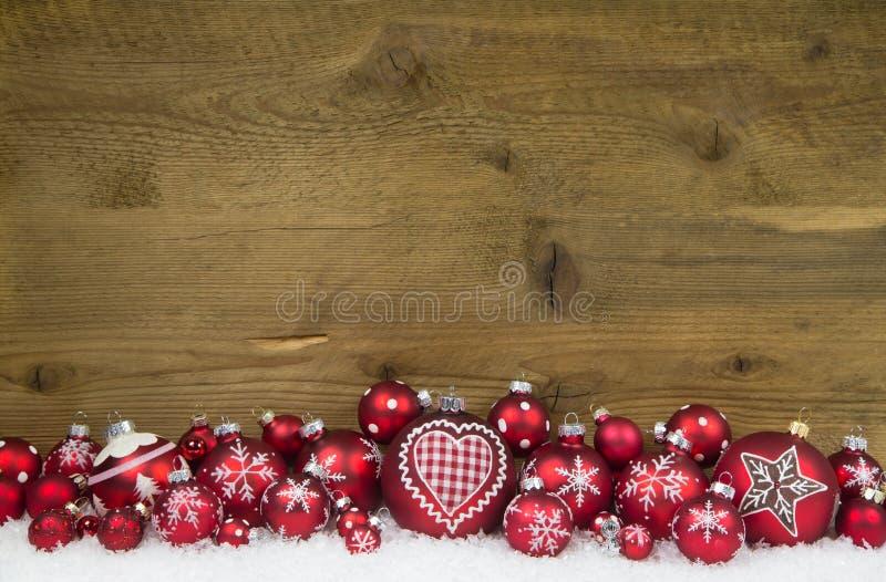 Julbakgrund av trä dekorerade med röda bollar och snö arkivfoto