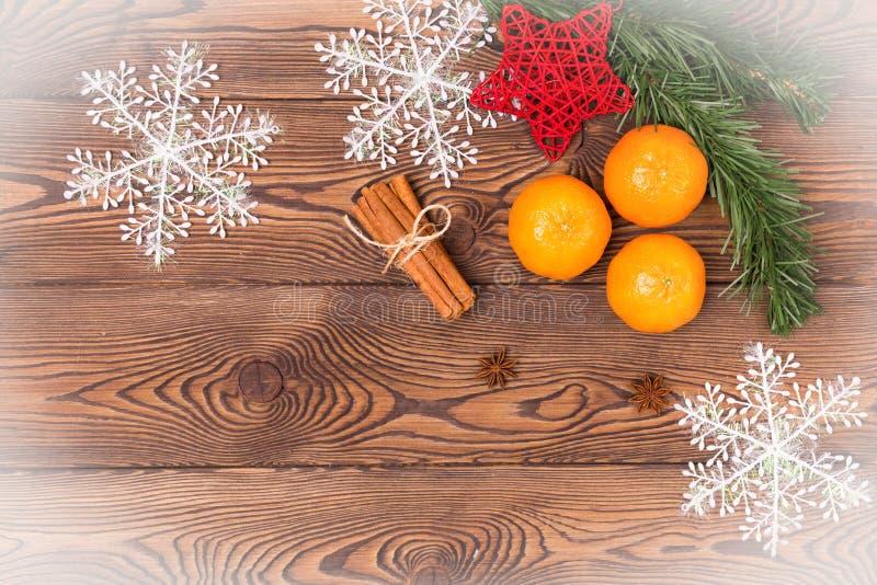 Julbakgrund - gammalt trä, granfilialer, sörjer kotten, snöflingor och tangerin, det nya årets dekor Lekmanna- lägenhet, kopierin royaltyfria bilder