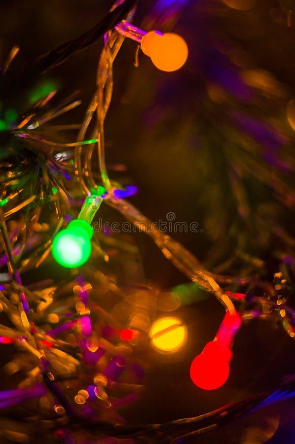 Julbakgrund-girlander med färgrika ljus på en dekorerad julgran, bokeh royaltyfria foton