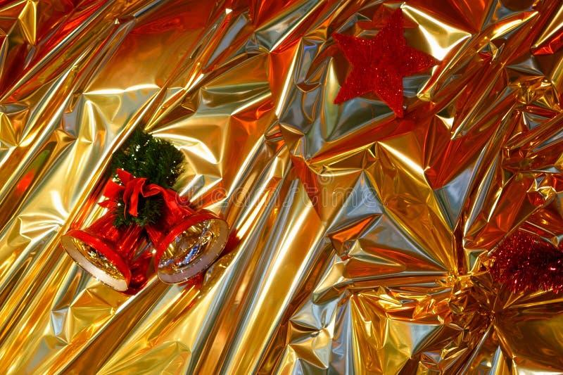 Julbakgrund, guld-färgat inpackningspapper, en röd julstjärna och skinande julklockor arkivbilder