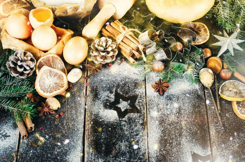 Julbakgrund - kottar, granträd, deg, mjöl, kavel, ägg, äggyolksover, kryddor, torra apelsiner, gammalt mörker arkivbild