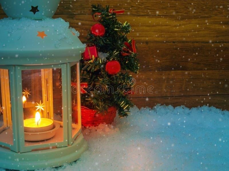 Julbakgrund, med belysninglyktan och dekorerat sörjer trädet i snön royaltyfria foton
