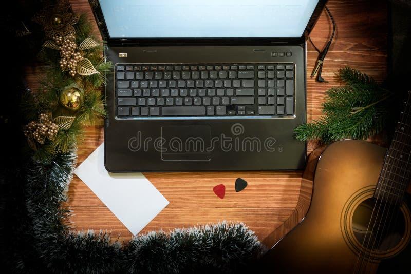 Julbakgrund med den akustiska gitarren, bärbar dator, kopieringsutrymme arkivbilder