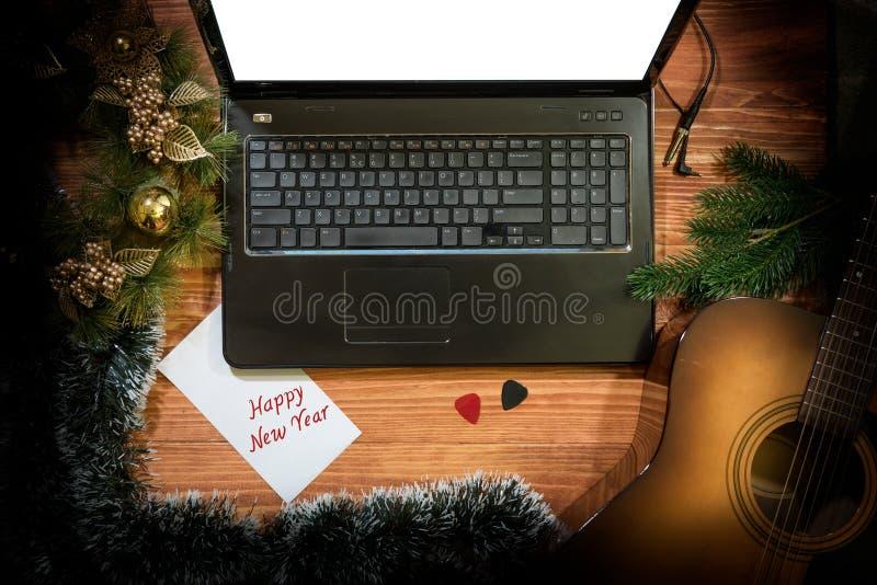 Julbakgrund med den akustiska gitarren, bärbar dator, kopieringsutrymme arkivfoto