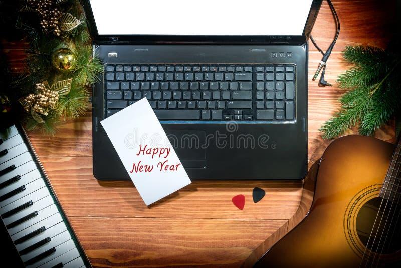 Julbakgrund med den akustiska gitarren, musikaliskt tangentbord, bärbar dator, kopieringsutrymme arkivfoto