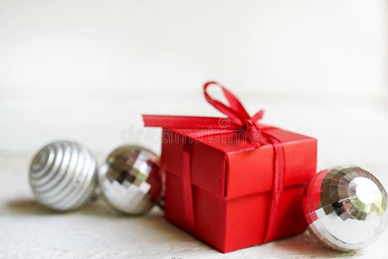 Julbakgrund med den röda gåvan, bollar för nytt år på vit bakgrund Lägga framlänges, kopieringsutrymme, hälsningkort royaltyfri foto