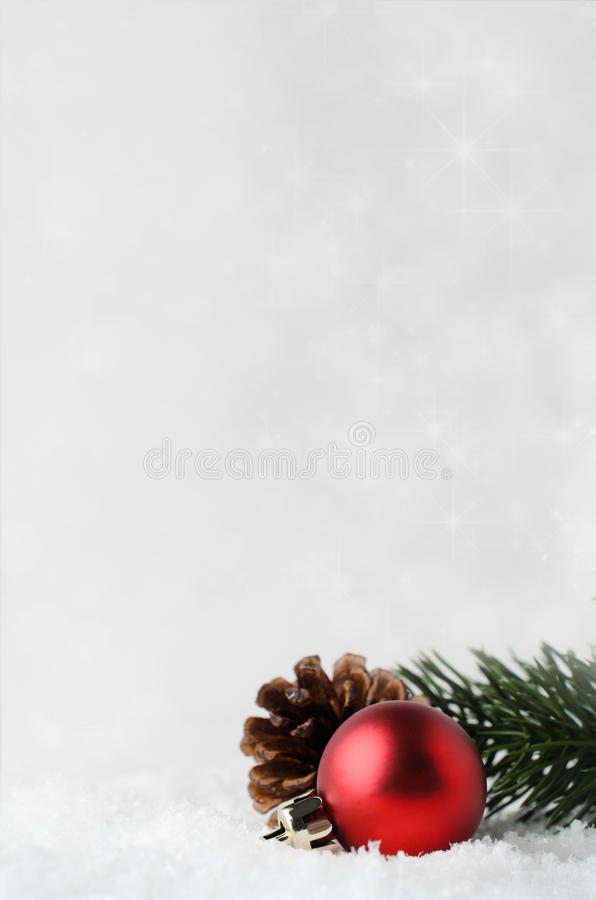 Julbakgrund med den röda struntsaken och lövverk på snö royaltyfri bild