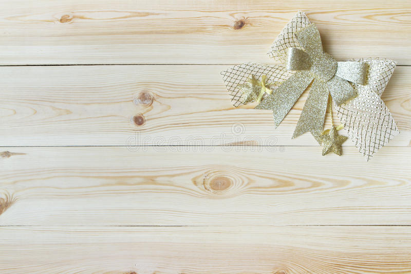 Julbakgrund med den trä och guld- pilbågen royaltyfria foton