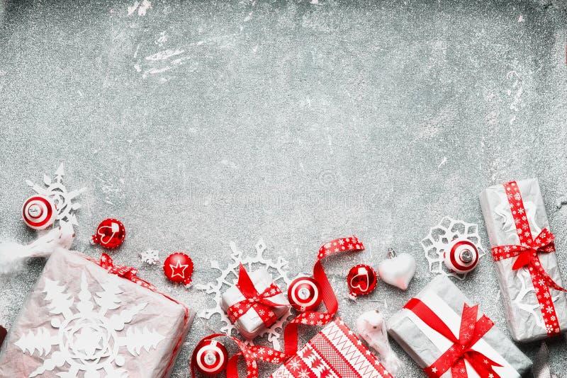 Julbakgrund med den vita röda gåvasjalen, festliga feriegarneringar och snöflingor för handgjort papper, bästa sikt royaltyfri bild