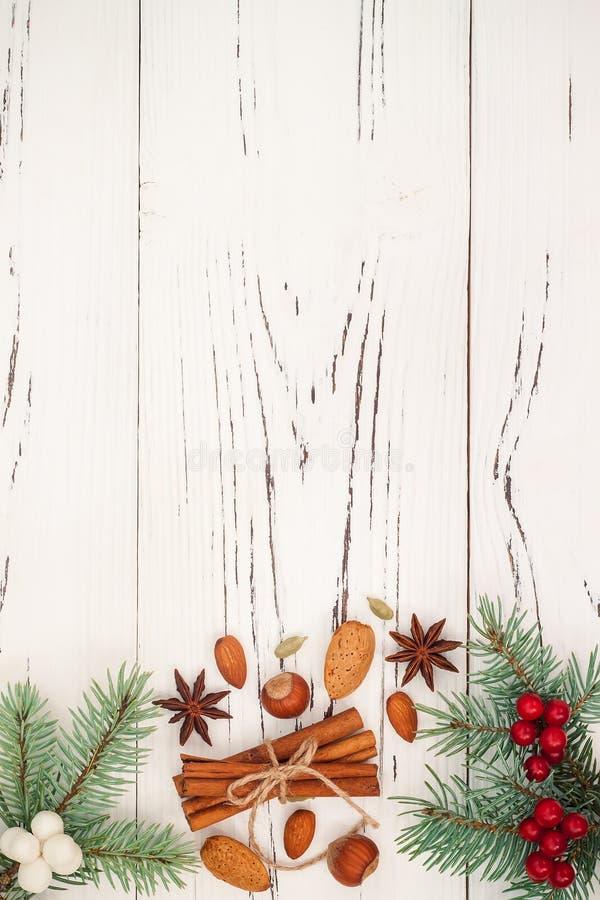 Julbakgrund med gåvor, gran förgrena sig och kryddor på det gamla träbrädet med kopieringsutrymme arkivbild