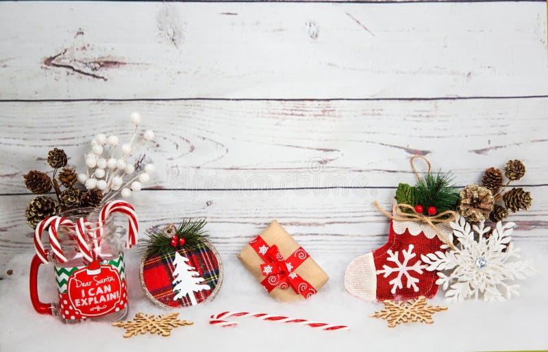 Julbakgrund med garneringar och gåvaask på det vita träbrädet arkivbild