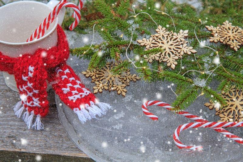 Julbakgrund med granfilialer, dekorerade snöflingor och godisrottingar på isen i tappning utformar royaltyfri fotografi