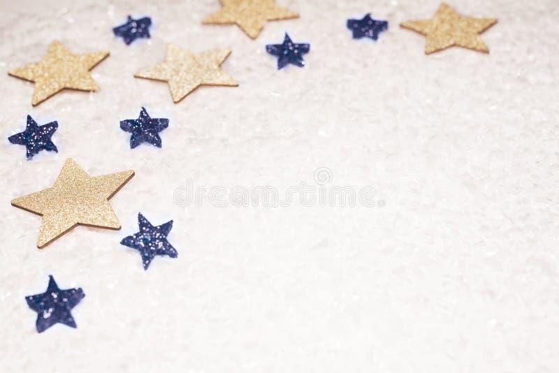 Julbakgrund, med guld- och blått blänker stjärnor och snö arkivfoton