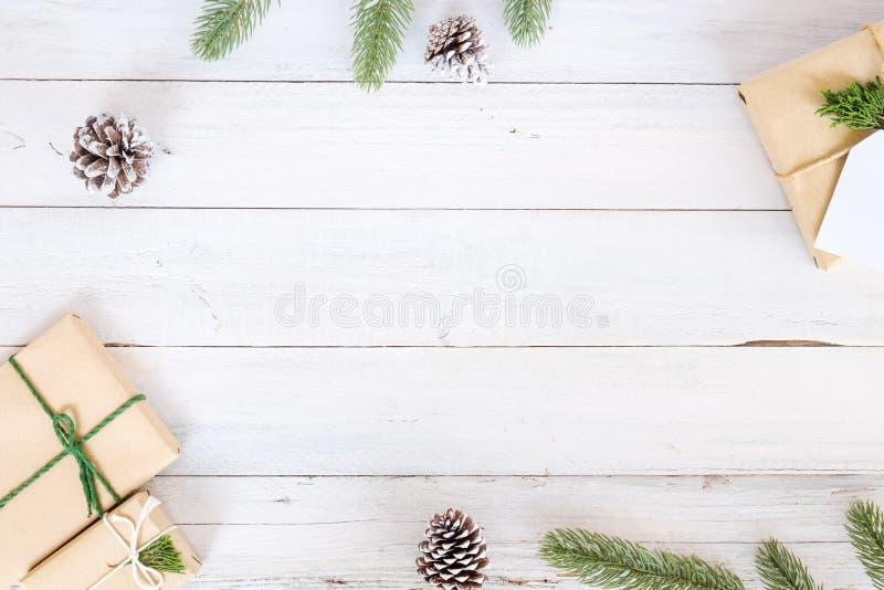 Julbakgrund med handgjorda närvarande gåvaaskar och lantlig garnering på det vita träbrädet royaltyfri foto