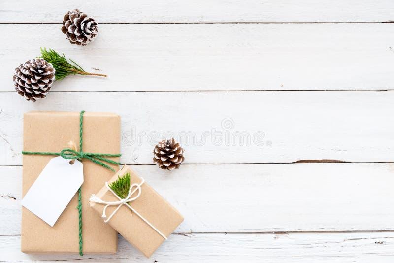 Julbakgrund med handgjorda närvarande gåvaaskar och lantlig garnering på det vita träbrädet royaltyfri bild
