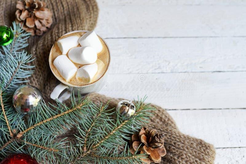 Julbakgrund med kaffekoppen och garnering av leksaker och att sörja trädet på den vita trätabellen, kopieringsutrymme arkivbild
