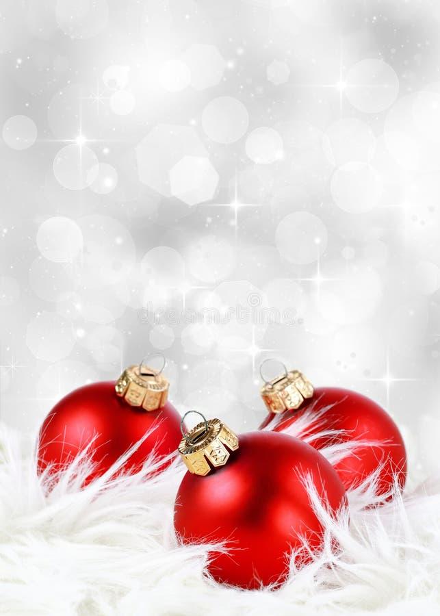 Julbakgrund med röda prydnader på fjädrar och en silverbakgrund fotografering för bildbyråer