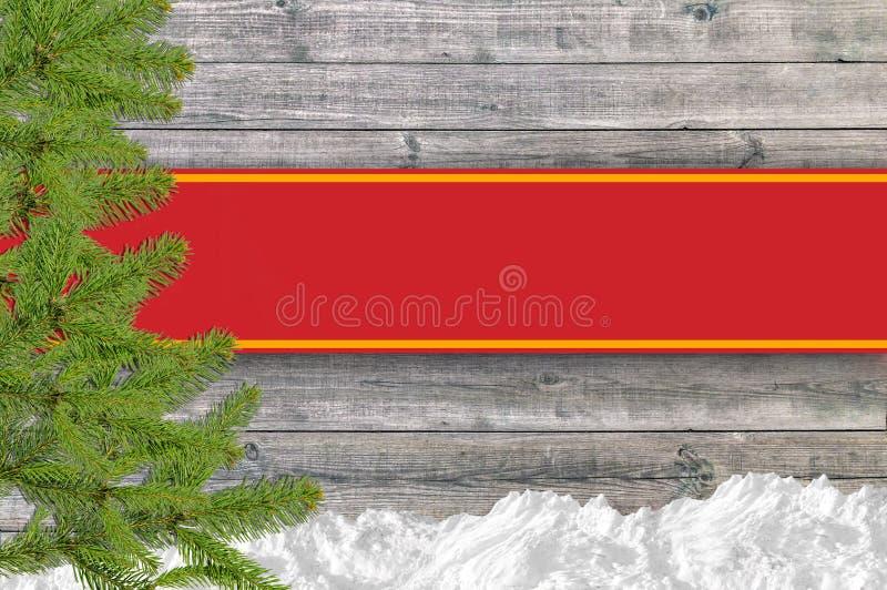 Julbakgrund med snö sörjer trädet och det röda bandet arkivfoto