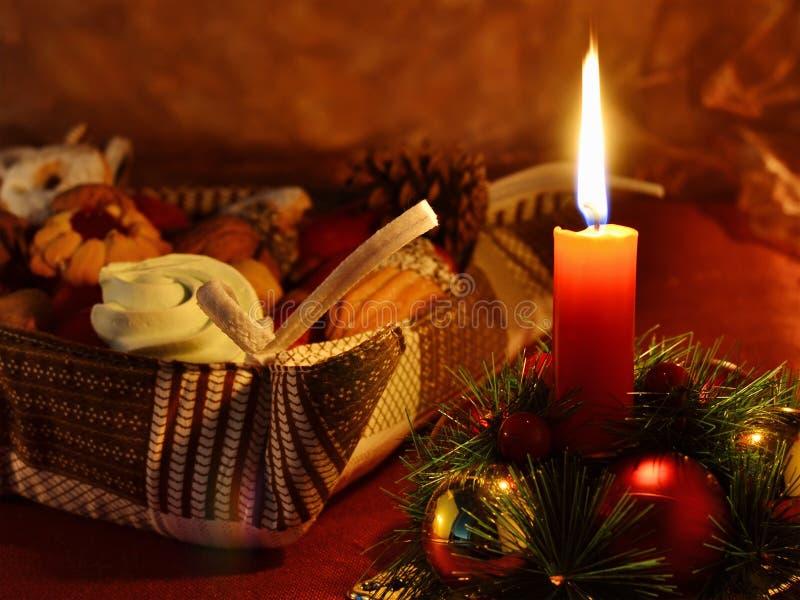 Julbakgrund med stearinljuset, kransen, kakor och garneringar arkivbild