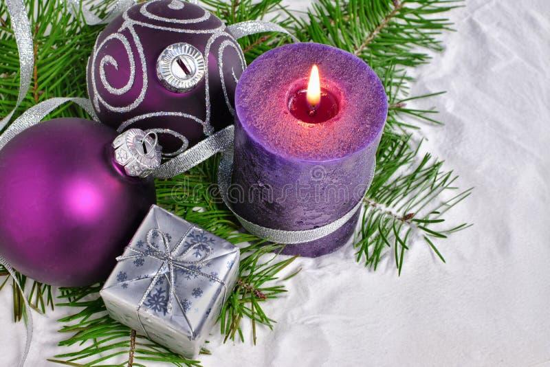 Julbakgrund med stearinljuset och garneringar Lilor och silverjulbollar över granfilialer i snön arkivfoto