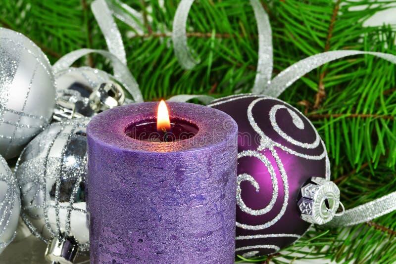 Julbakgrund med stearinljuset och garneringar Lilor och silverjulbollar över granträdfilialer i snön royaltyfri foto