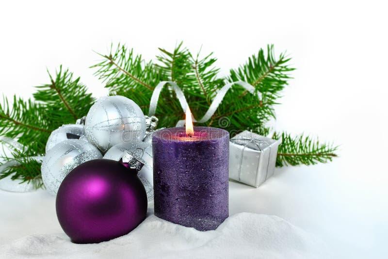 Julbakgrund med stearinljuset och garneringar Lilor och silverjulbollar över granträdfilialer i snön royaltyfri fotografi