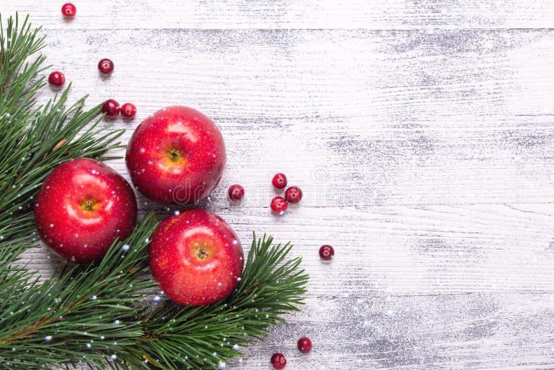 Julbakgrund med trädfilialer, röda äpplen och tranbär Ljus trätabell Snöfall som drar effekt arkivbild