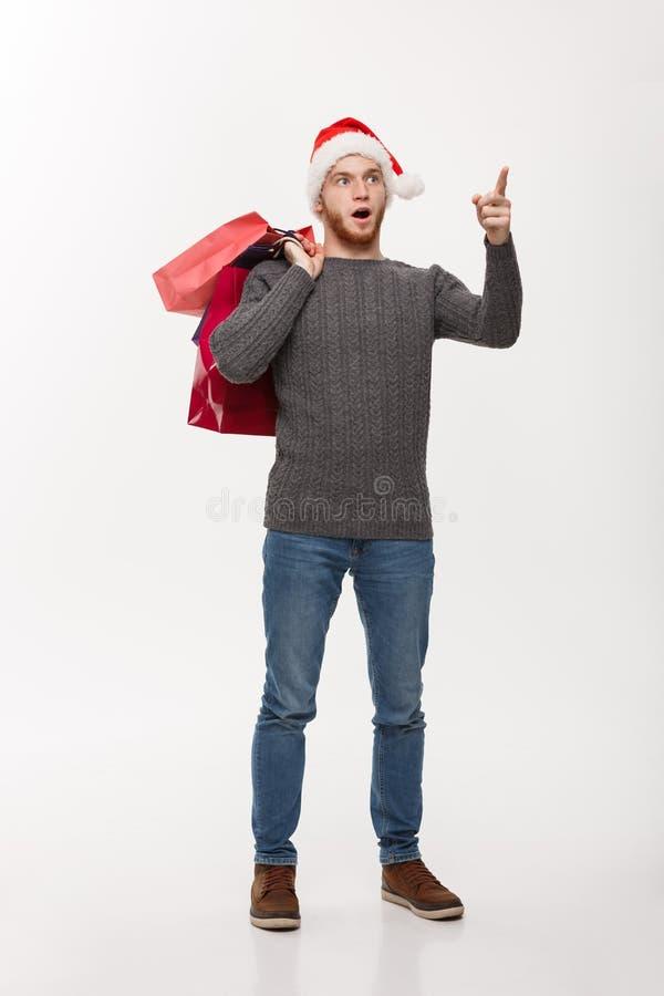Julbegrepp - överraskande chockerande hållande shoppingpåse för attraktiv ung caucasian man och pekafinger framme royaltyfri bild
