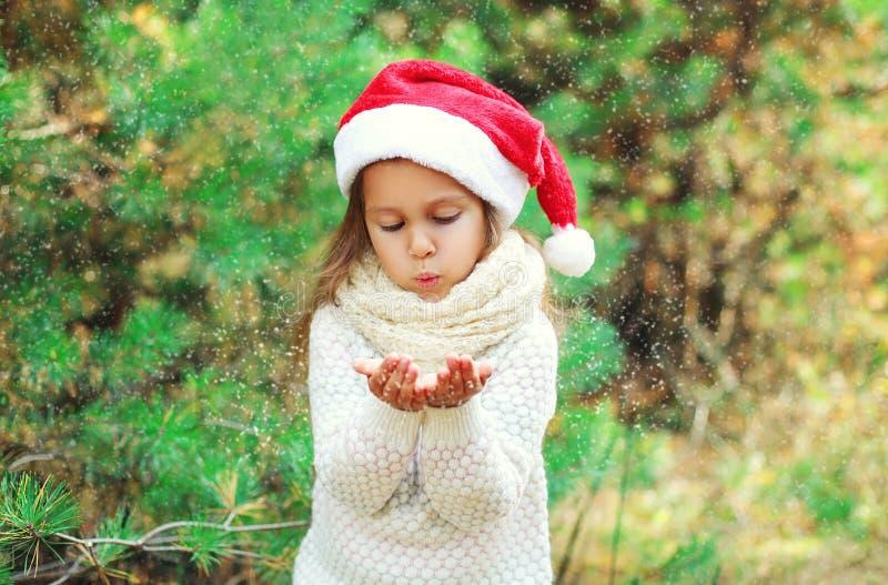 Julbegrepp - liten flickabarn i santa den röda hatten som blåser på insnöade händer arkivbilder